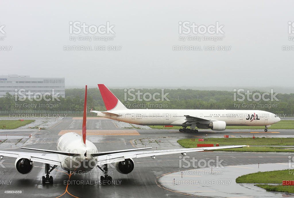 Japan Airlines (JAL) aircraft are in line on the runway royalty-free stock photo