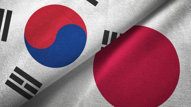 japan en zuid-korea twee vlaggen samen textiel doek stof textuur - korea stockfoto's en -beelden