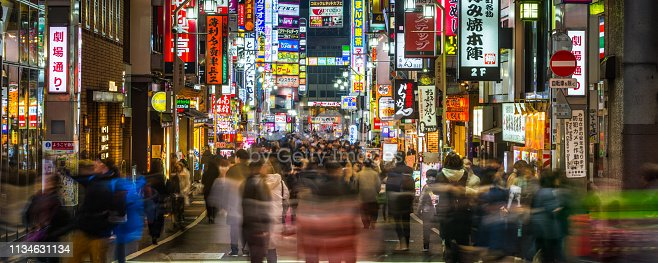 Crowds of shoppers, commuters and tourists thronging the pedestrianised streets of Kabukicho in the Shinjuku district of central Tokyo at night, Japan.