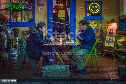 istock Japan nightlife senior couple drinking al fresco pavement bar Osaka 695484676
