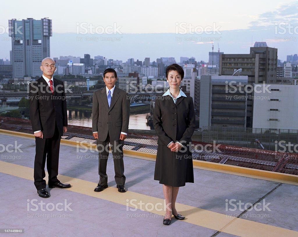 Japan, Tokyo, Shibaura, three executives standing on rooftop, po royalty-free stock photo