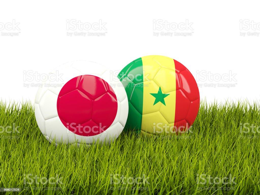 Japão vs Senegal. Conceito de futebol. Bolas de futebol com bandeiras na grama verde - foto de acervo