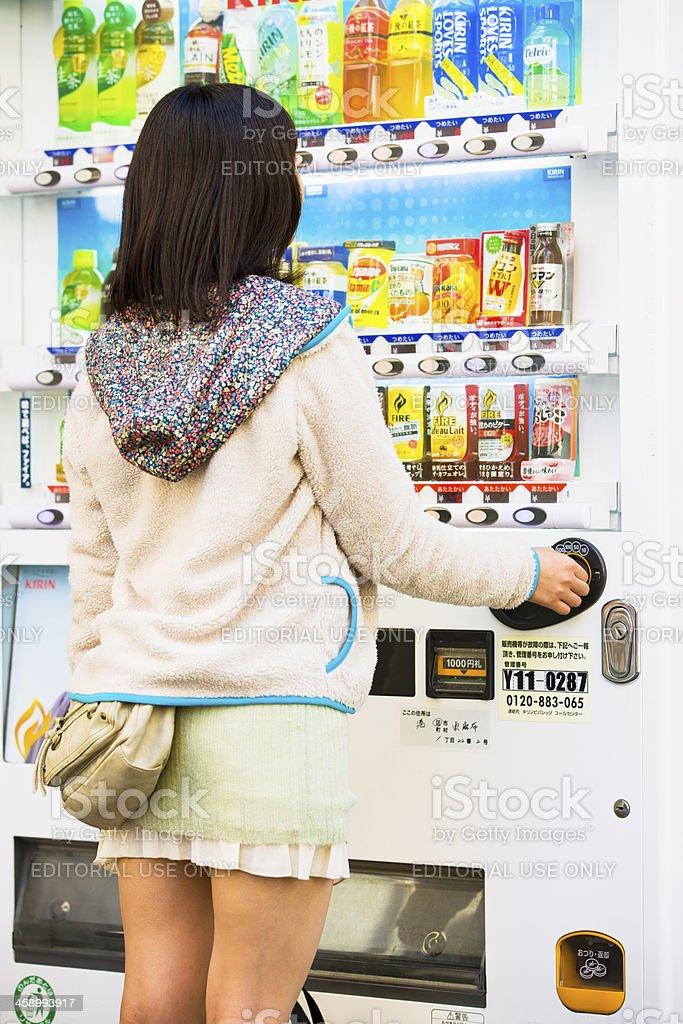 Japan, woman at beverage vending machine royalty-free stock photo
