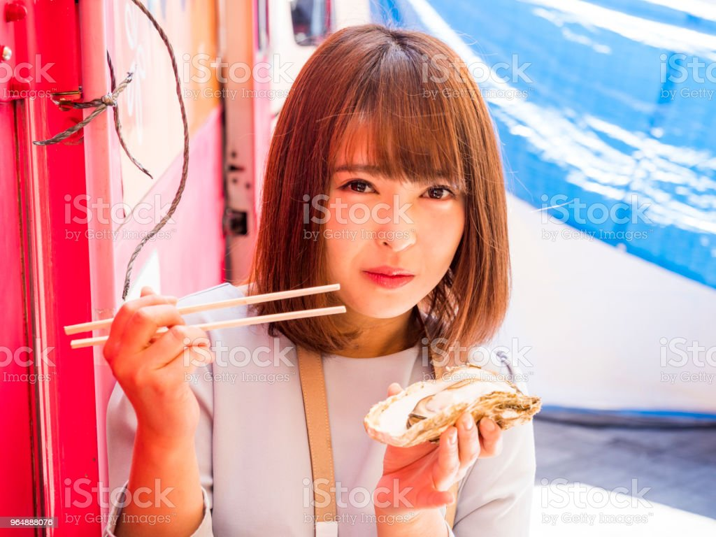 Japanes young lady eating at the food truck. royalty-free stock photo