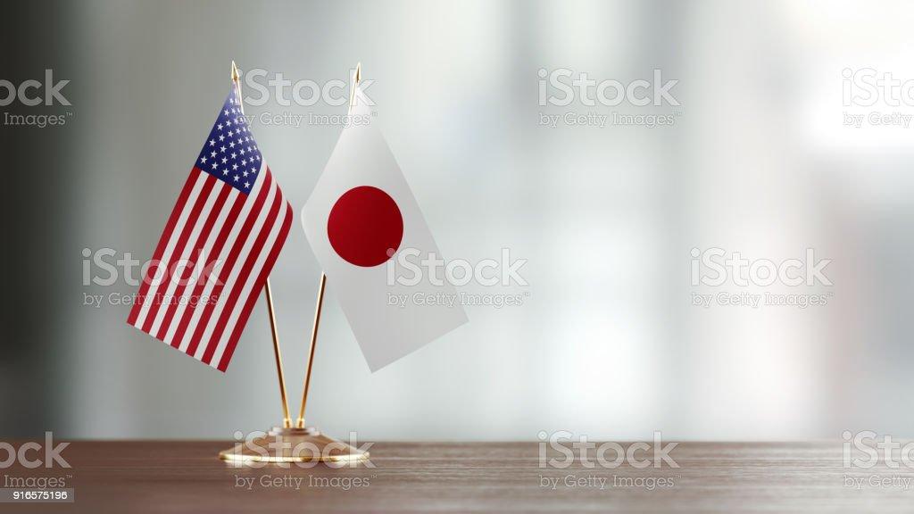Par de bandeira japonesa e americana em uma mesa sobre fundo desfocado - foto de acervo