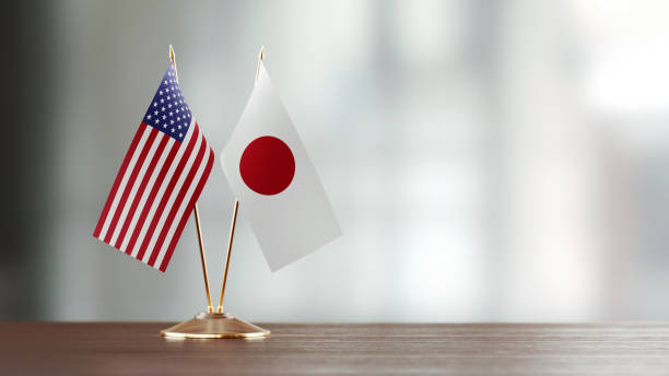 Japanese And American Flag Pair On A Desk Over Defocused Background stock photo