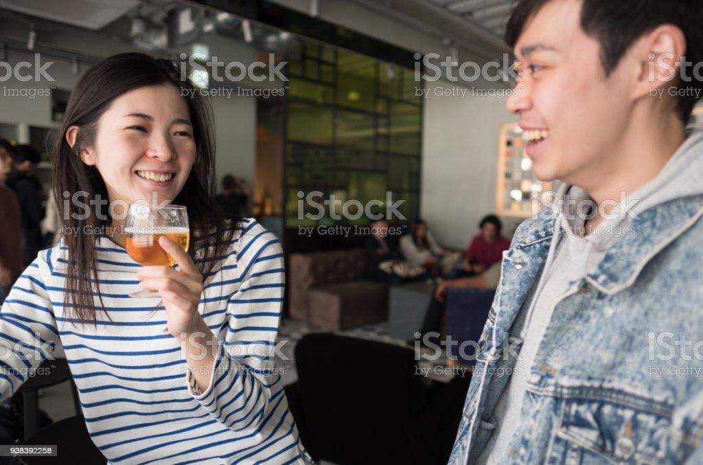 ハッピーアワーでビールを飲みながら日本語と混合レース カップル ストックフォト