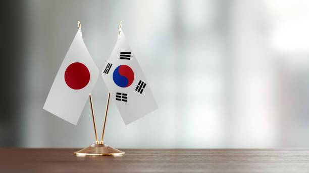 日本と韓国の国旗ペア多重の背景の上の机の上 - 韓国 ストックフォトと画像