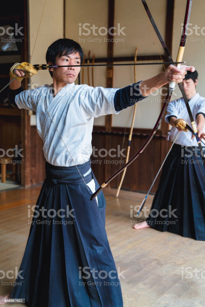 Japanese archer draws his bow ready to fire stock photo