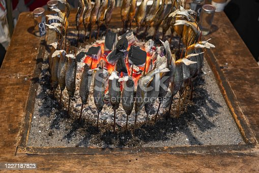 Japanese ayu fish skewers also called sweetfish grilled with salt and cooked in circle in a traditional robatayaki cooking around hot charcoals on a irori sunken hearth.
