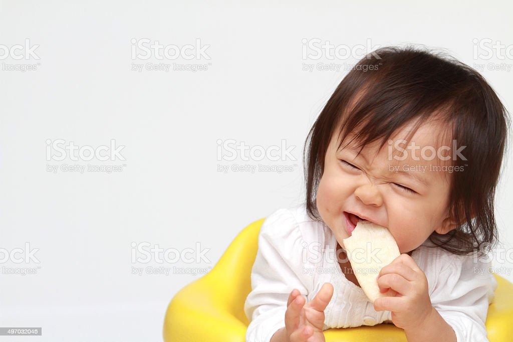 Japanese Bebê Menina comendo biscoitos de arroz - foto de acervo