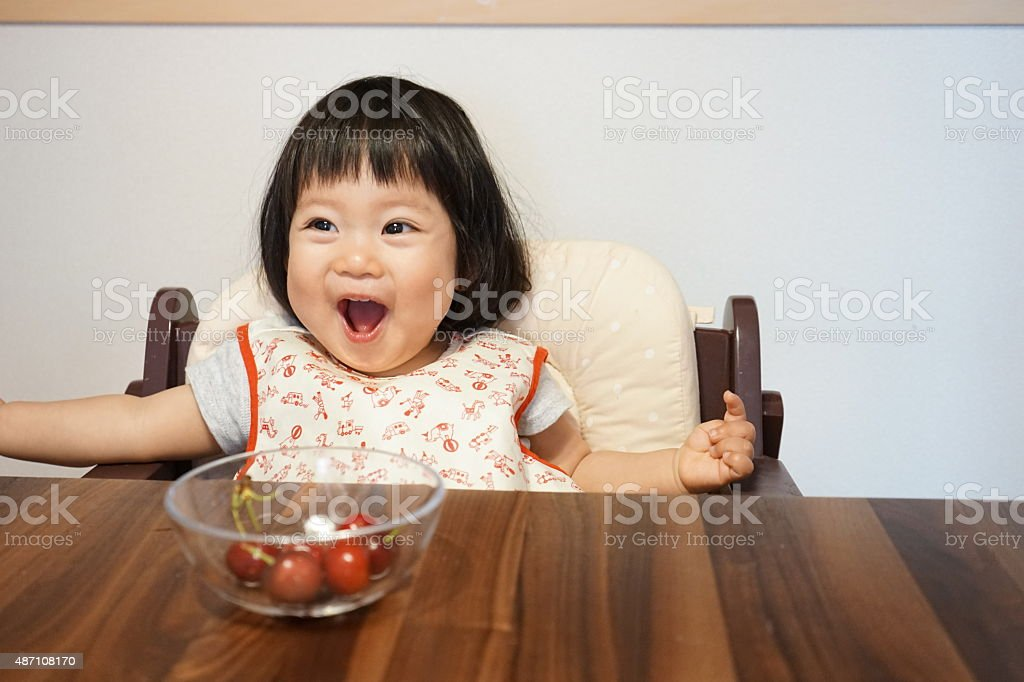 Japanese baby girl is happy with fruits(cherry and banana) stock photo