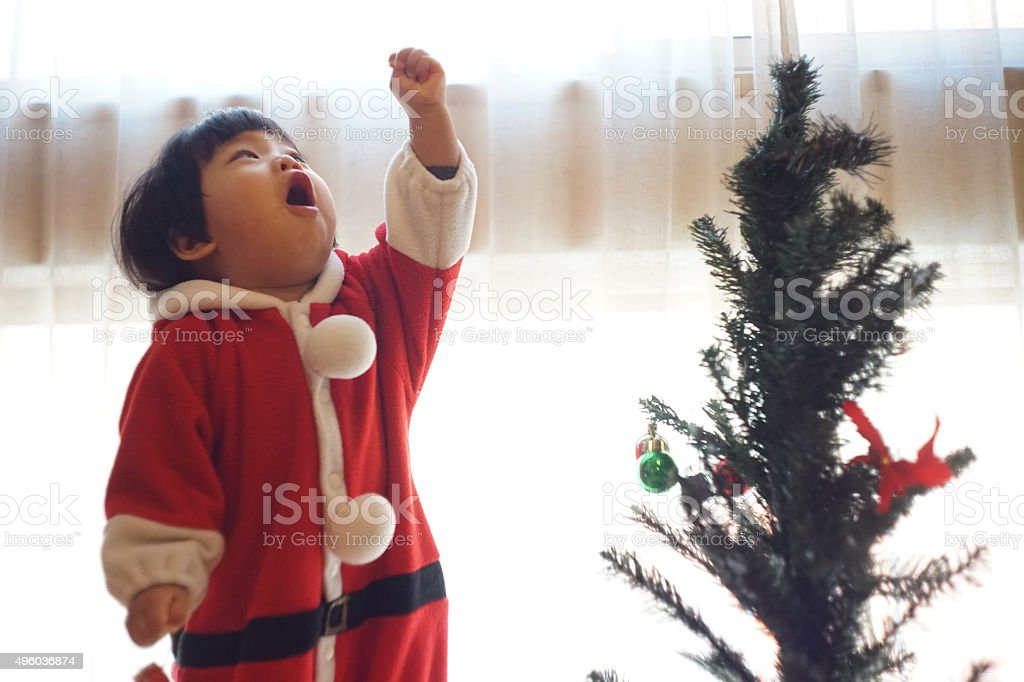 Japanese Baby Girl Is Trimming a Christmas Tree stock photo