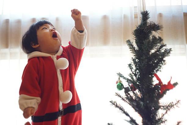 japanische baby mädchen ist ein weihnachtsbaum schneiden - weihnachten japan stock-fotos und bilder