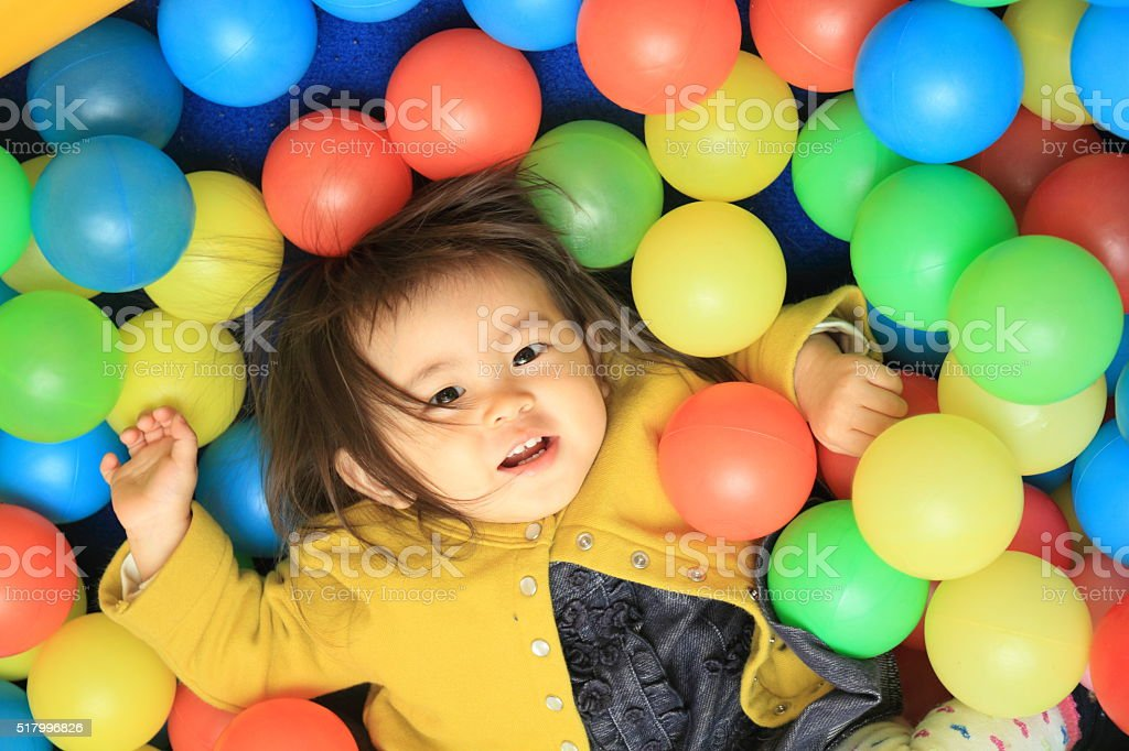 Japanese baby girl playing in ball pool (1 year old) stock photo