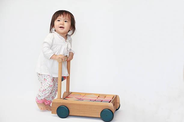 Japanese baby girl pushing a cart (1 year old) stock photo