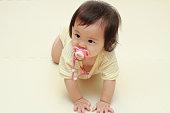 日本の赤ちゃんのおしゃぶりをなめる少女