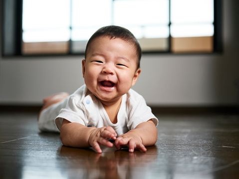 A six month old Japanese baby boy inside a home.