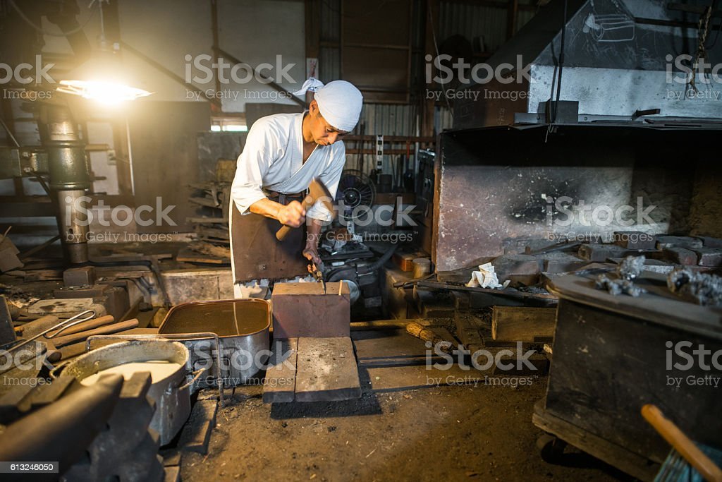 Japanese blacksmith hammers hot steel in his forge圖像檔