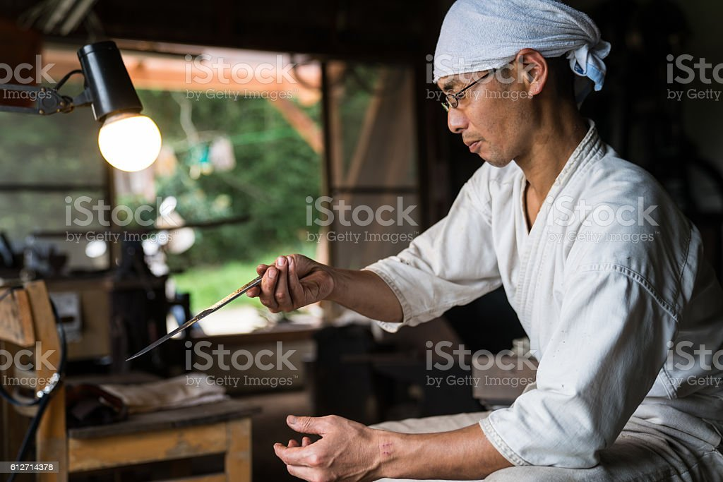 Japanese blacksmith inspecting the quality of a knife blade圖像檔