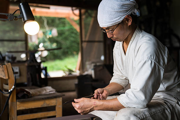Japanese blacksmith inspecting the quality of a knife blade stock photo