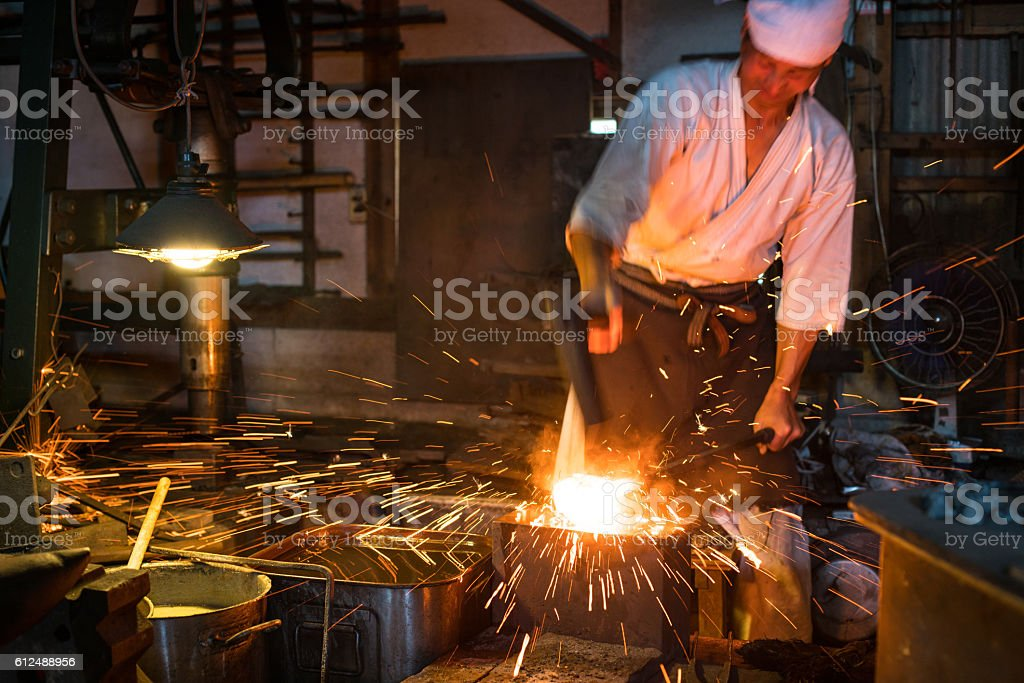 Japanese blacksmith pounds red hot steel while forging a sword圖像檔