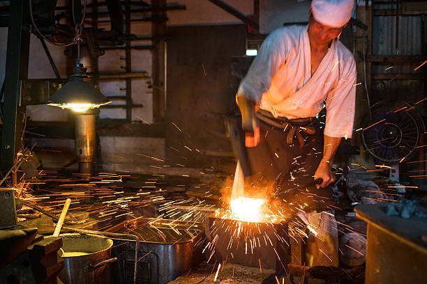 Japanese blacksmith pounds red hot steel while forging a sword stock photo