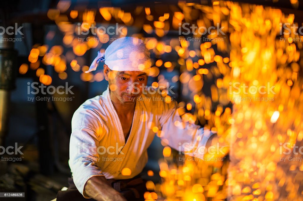 Japanese blacksmith stokes a fire preparing to forge a sword stock photo