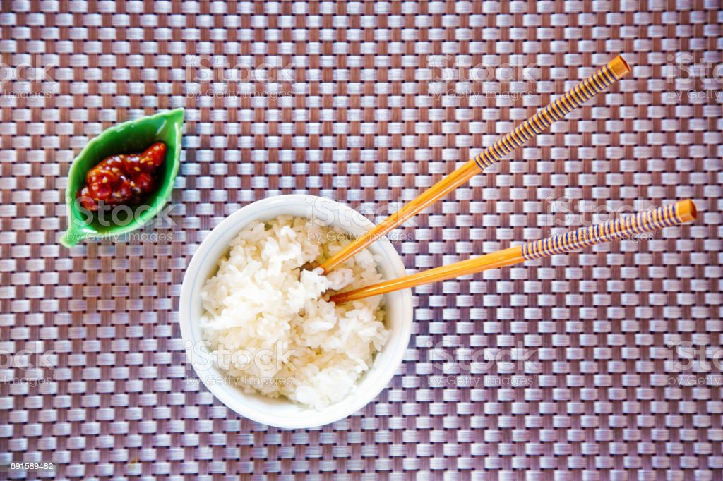 Japanese bowl of rice with chopsticks and pickles over tatami place meat stock photo