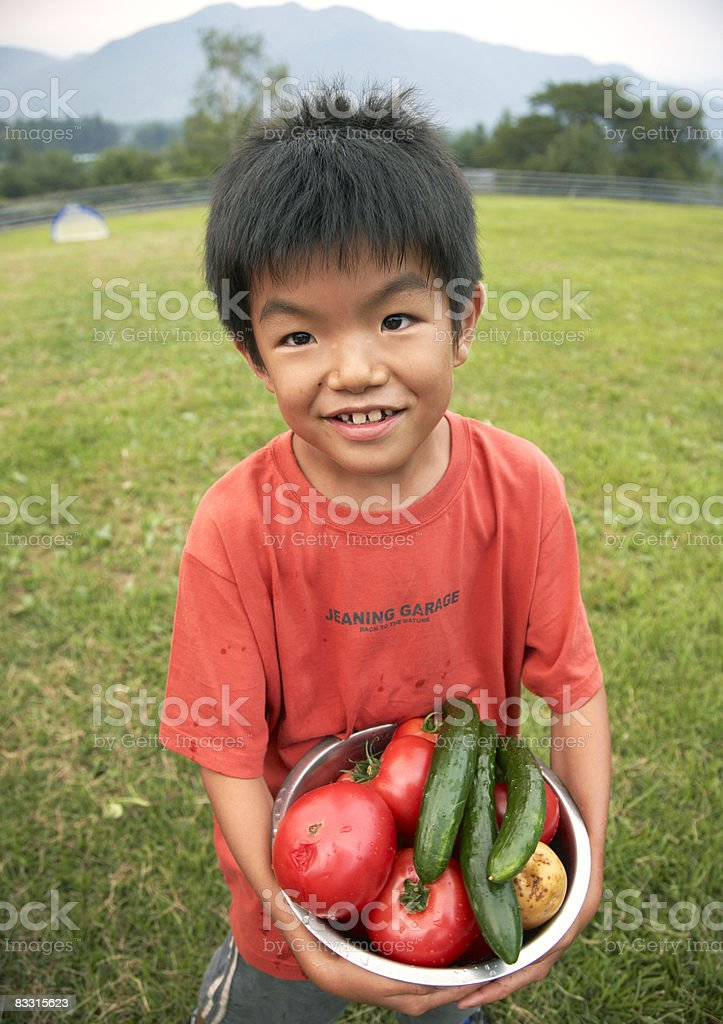 Japanese boy holding vegetables royaltyfri bildbanksbilder