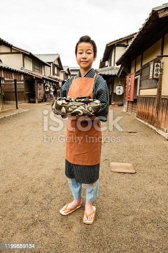 This is a portrait of a Japanese boy wearing old fashioned clothing as he holds a wrapped package as  he stands outdoors on a set themed as a rural Village's Main Street.