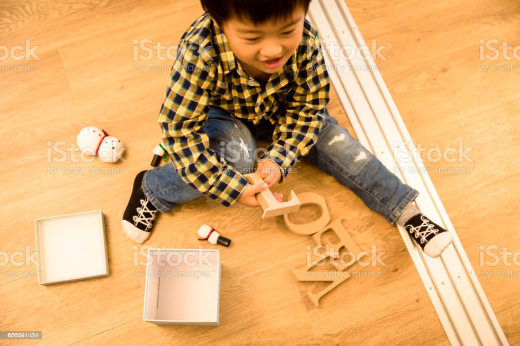 A Japanese boy is sitting on the flooring floor and playing with a...
