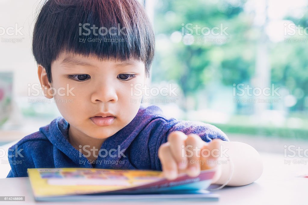 Japanese boy is reading a educational play book. stock photo