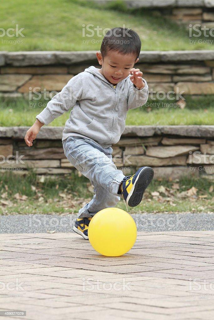 Japanese boy kicking a yellow ball stock photo