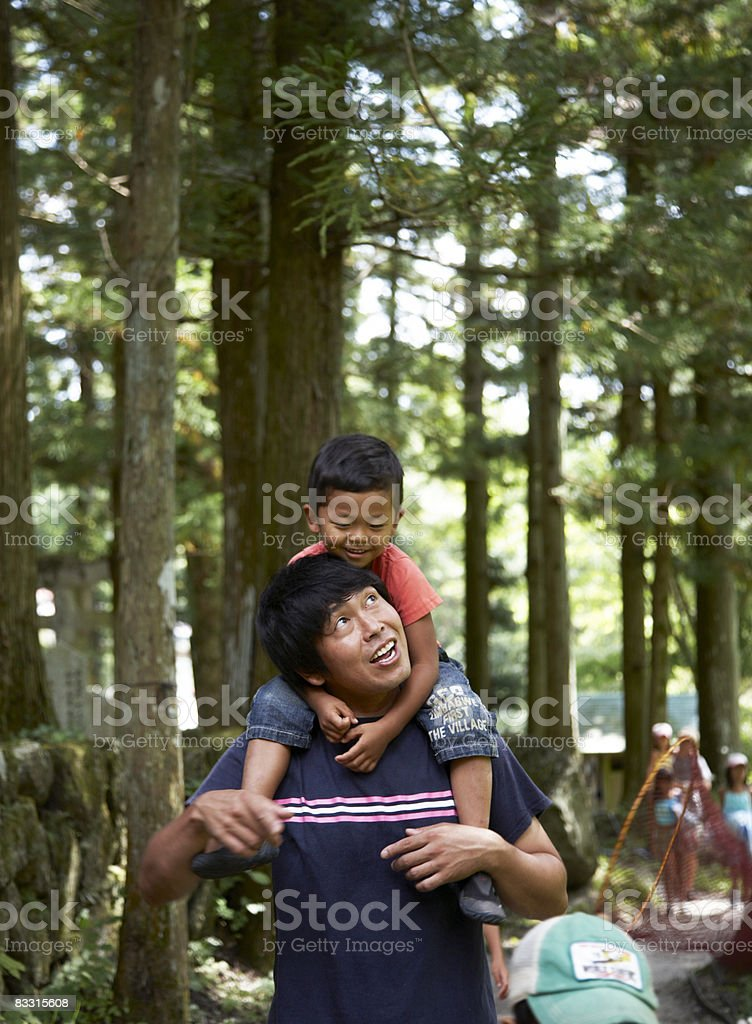 Japanese boy on his father's shoulders, smiling royalty free stockfoto