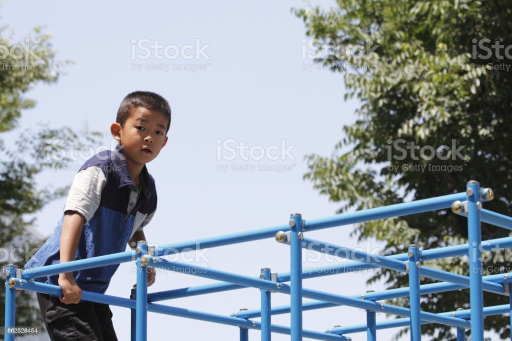 Japanese boy on the jungle gym (second grade at elementary school) stock photo