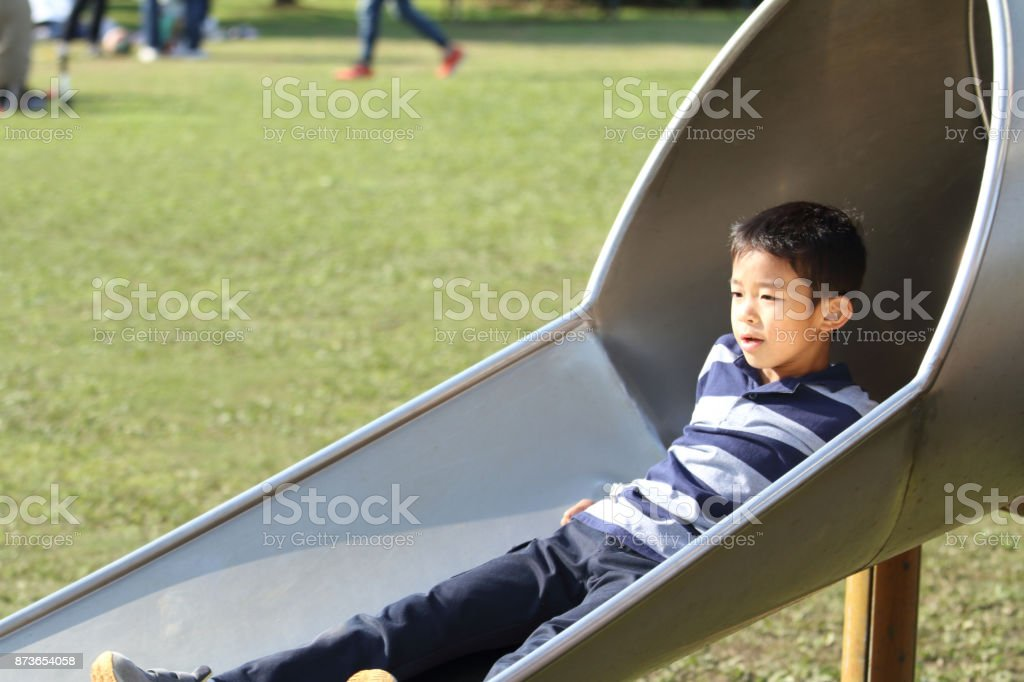 Japanese boy on the slide (second grade at elementary school) stock photo