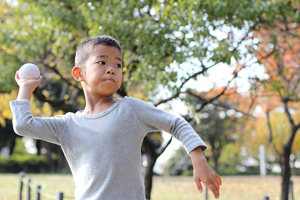 Japanese boy playing catch Japanese boy playing catch (first grade at elementary school) throwing stock pictures, royalty-free photos & images