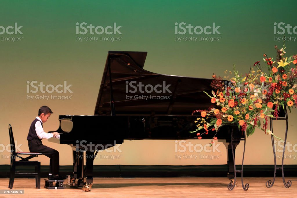 Japanese boy playing piano on stage (second grade at elementary school) stock photo