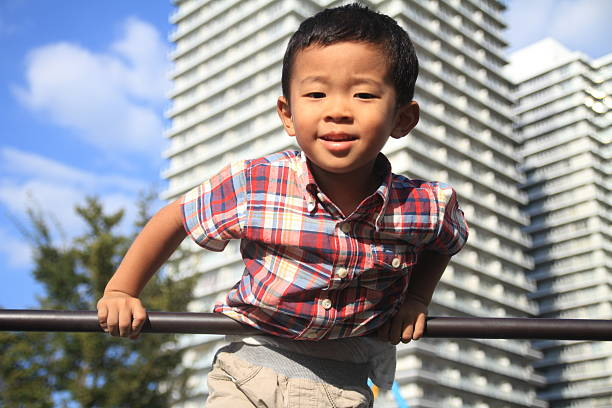 japanese boy playing with high bar - horizontal bar stock photos and pictures