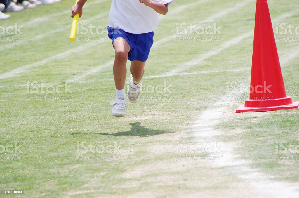 Japanese boy running in a relay race on a grass track stock photo
