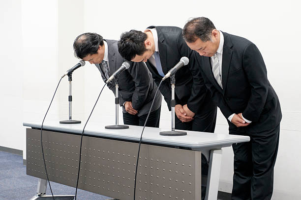 Japanese Business Apology A group of Japanese business people bowing to apologize as a form of shazaikaiken. Taken on location in Kyoto, Japan. apologist stock pictures, royalty-free photos & images