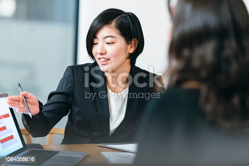 istock Japanese business consultant giving advice to her client at home 1064058616