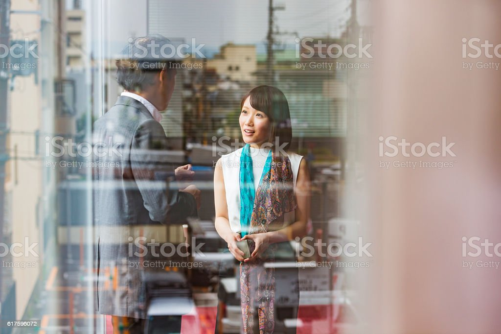 Japanese Business Man and Woman Meeting Viewed Through Office Window stock photo