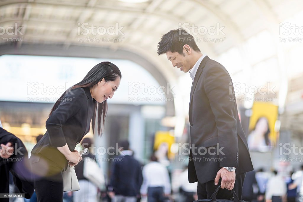 Japanese business people bowing to each other at station stock photo