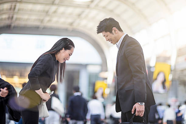 japanese business people bowing to each other at station - お礼 ストックフォトと画像