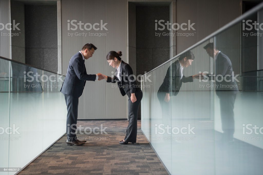 Japanese business people shaking hands and bowing stock photo