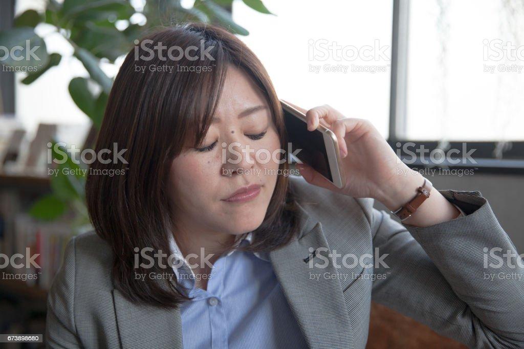 Femme d'affaires japonaise répondant à l'appel photo libre de droits
