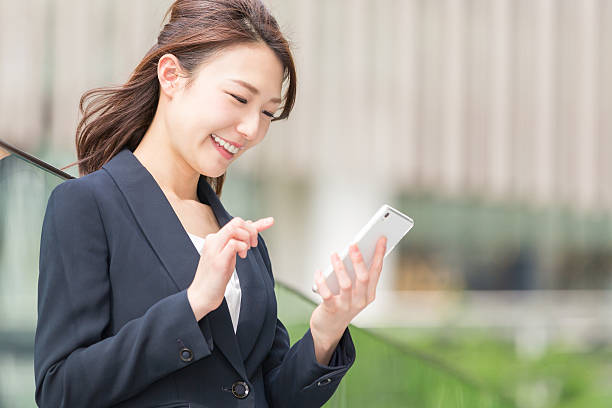 japanese business woman holding a smart phone - スマホ 女性 ストックフォトと画像