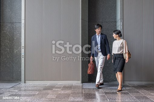 istock Japanese Businessman and Businesswoman Exiting Elevator in Modern Office Building 539357384